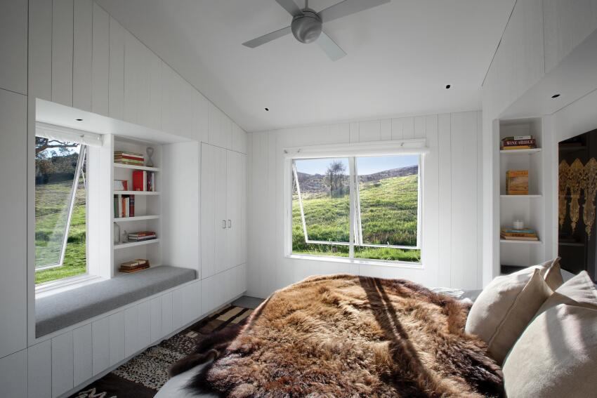Living spaces such as the master bedroom, children's bunkroom, and master bath are also located under the eaves on either side of the central living space. Finishes remain elemental throughout, with operable aluminum windows and painted wood walls in the bedroom.