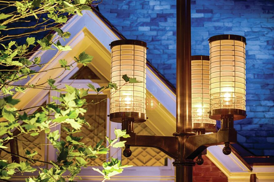 A detail view of the custom-designed pole-mounted glass lanterns in the courtyard dining area.