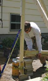 "Before raising the post, the base of the 2x4 ""assistant"" is attached to the post's concrete pier with a nylon load strap and secured plumb with the braces."