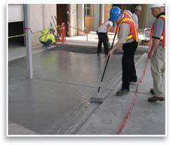 Workers brush on the epoxy bonding agent to provide a bond between the concrete and mortar.
