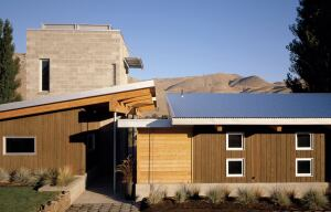 A shaded passageway between the home's two buildings holds the entries to both wings. The structures' forms and corrugated metal roofs resemble those of local fruitstorage facilities, tying them to the region's strong agricultural history.
