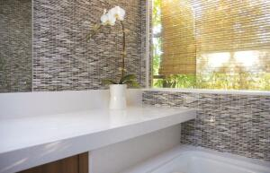 Fry Reglet Corp. produces a plentiful supply of channels and trim pieces that help solve transition problems. For this bath, Slant Studio used Fry reveals at the corners of the window and between the tile and mirror.