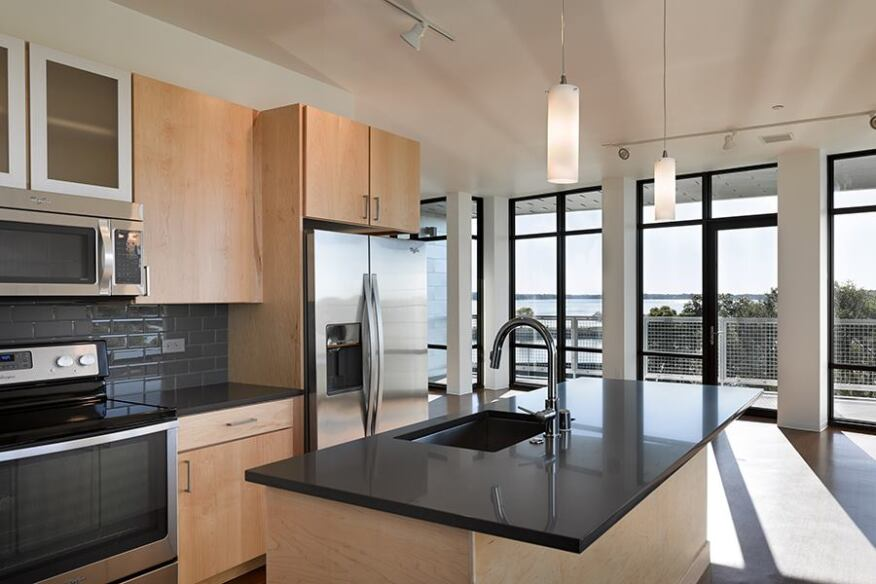 Kitchens at Seven27 feature quartz countertops; subway-tiled backsplashes; and wood cabinets, some with glass fronts.