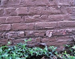 Painting a brick masonry wall can do more harm than good, by trapping moisture which damages the wall's surface.