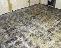After removing linoleum tile and scraping away the loose mastic from this wood underlayment.