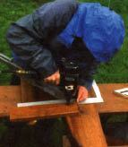 Figure 7. The author uses a framing square to be sure the seat-support 2x4s are at the correct 5-degree angle — which is a 1-in-12 pitch — as he nails them to the 4x10 posts.