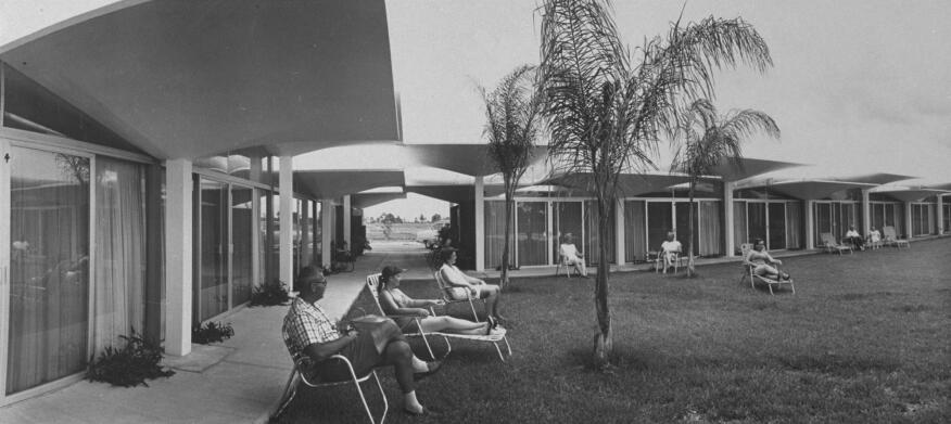 People relaxing in lounge chairs in courtyard at new resort motel with a parasol roof made of 75 concrete umbrellas joined with plastic.