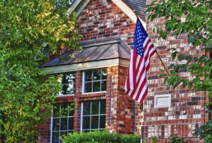 Patriotic American flag displayed in front of southern home