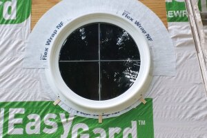 A flexible butyl-based flashing material works well for flashing roundtop windows, but the sill is tricky. In this case, the installer has left the bottom uncaulked and added shims to promote drainage.