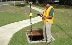 Asset management coordinator Rocky Agbunag uses a Trimble ProXT GPS receiver  and a Panasonic Toughbook CF18 tablet PC to collect the point location and  associated data on an inlet in a St. Johns County neighborhood. A Trimble  GeoBeacon, about midway up the GPS pole, enables in-the-field data processing. Photo: St. Johns  County, Fla.