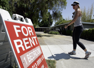 """Image of """"renter"""" who's checking out a """"for rent"""" sign"""