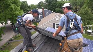 Technicians Mel Janarelli and Brandon Bernard set a solar panel on the roof of a 1960's-built house.