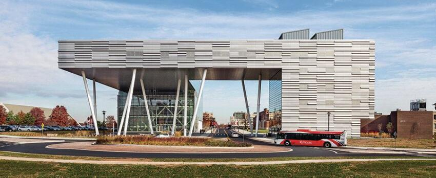 The building's southwest corner, supported by canted columns, bridges a road onto the campus. Three-dimensional metal panels from Metalwërks clad the west and south façades.
