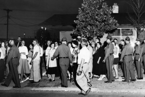 State police carrying riot sticks push back residents, Aug. 20, 1957 in Levittown, Pa., near the home of Mr. and Mrs. William Myers, the first black family to move into this planned community of previously all-white residents. One man was arrested in what police said was a rock throwing in which a State trooper was struck. (AP Photo/Sam Myers)