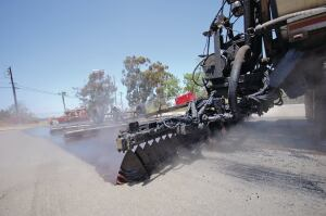 Scrub/sand sealing. Emulsion is applied with a computer rate-controlled distributor truck that drags a hydraulic broom. The broom works the liquid asphalt into cracks, sealing them and allowing a bond to form with the material that's placed on top (in this case, sand and fine aggregate). The surface is then rolled and compacted and can be returned to traffic in a few hours.