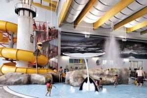 The Oregon-themed aquatics complex is a focal point for the facility. Play features for all ages include a water slide that wraps around a scaled-down replica of the Yaquina Head lighthouse, north of Newport, Ore. The slide plunge pool is surrounded by rock theming and includes a blowhole modeled after a natural feature at Depoe Bay. The blowhole is activated as bathers plunge into the splash zone at the bottom of the slide. Other amenities are floor geysers, interactive spray features, a vortex, and a lazy river that winds through a forest of artificial coniferous trees and doubles as a resistance channel for exercise, therapy and rehabilitation.