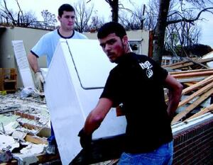 "SURVIVAL OF THE FITTEST: Above, a conventional house in Newburgh, Ind., had its roof ripped off by the  same storm that killed 18 residents of the Eastbrook Mobile Home Park. At  right, student volunteers salvage an appliance from a destroyed Newburgh  house. Strong tornadoes can destroy even well-constructed site-built homes; however, the  survival of even one interior room (or ""core element"") can  spell the difference between life and death."