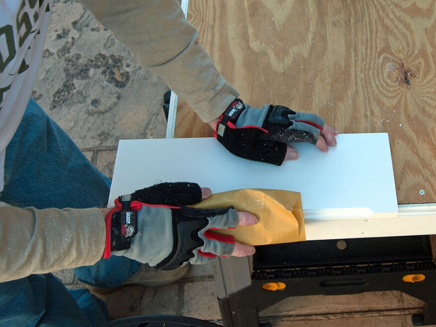 After cutting or routing PVC trim, the author gives the cut a light sanding with 320-grit paper.
