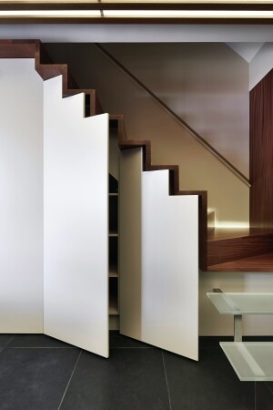 Stepped shelving in staircase of this D.C.-area home remodel by KUBE Architecture capitalizes on an otherwise unused space.