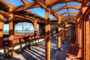 On a Craftsman-style home on Cape Cod, arched, red-cedar cross beams support a glass covering for this arbor.
