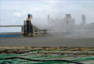 Fogging increases the surrounding relative humidity, so there is no need to  apply water to the concrete.