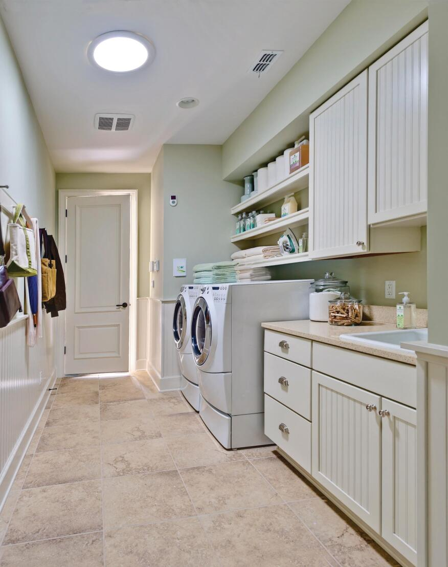Chores to Adore A combination mudroom/laundry off the garage includes pretty beadboard cabinets by Merillat, a Shaker peg rail for coats and bags, and a large utility sink for hand-washing clothes, flower arranging, or pet bathing. A sun tunnel overhead brings in natural light without electricity.