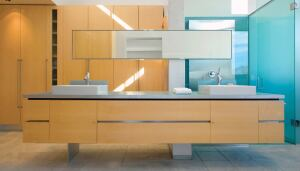 Wide drawers with recessed aluminum handles hold quotidian bathroom supplies; glass shelves behind a stainless steel shower screen house shampoo and soap.