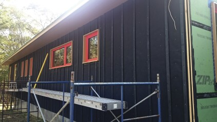 Black building paper, with 4-inch overlaps between courses, covers the side wall. To complete the drainage plane beneath the open plank siding, vertical strapping then attaches over the paper.
