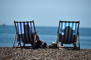 People sit on Brighton beach in Sussex, southern England, on July 17, 2014. Britons were sent scampering for shade as the temperature soared to 29.1C (84.4F), the highest level of the year so far. AFP PHOTO/BEN STANSALL        (Photo credit should read BEN STANSALL/AFP/Getty Images)
