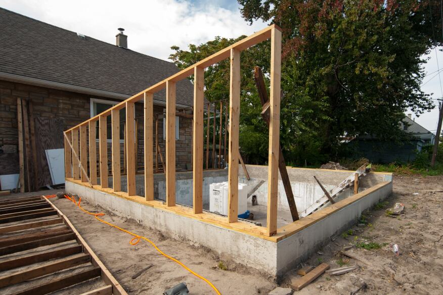 Structural insulated panel cutoffs line the perimeter of Afterhouse's foundation wall below and at grade. The crew is framing the structure's walls with lumber salvaged from the original house.