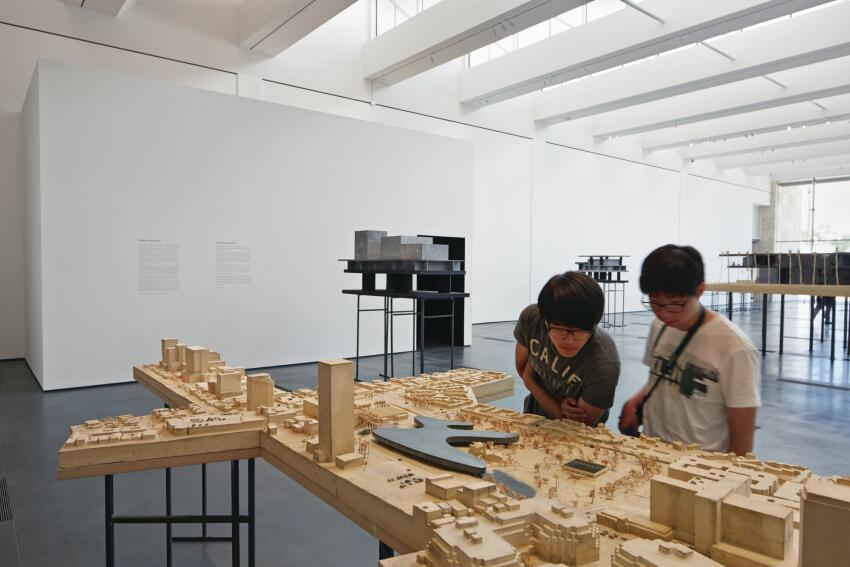 Visitors at LACMA's Resnick Exhibition Pavilion survey Peter Zumthor's proposed model for the museum campus.