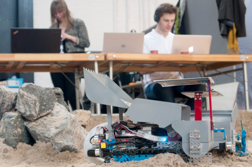 An autonomous robot from the MARS cluster rolls across the sandpit while researchers develop new logic for its movements.