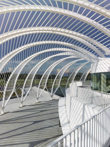 A white-painted pergola shades an outdoor terrace and plaza while reducing solar load on the building.