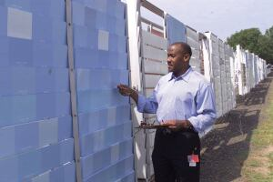 PAINT CHECK: Paint chemist Stewart O. Williams, Ph. D., inspects test samples at the Rohm and Haas long-term outdoor exposure facility in Pennsylvania.  Continued research has improved paint performance in recent years.