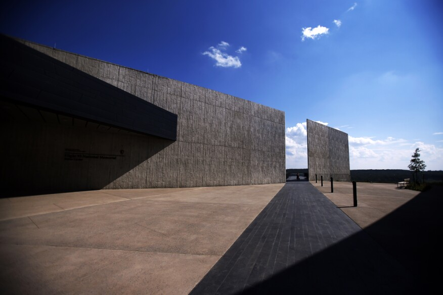 The flight path of United Airlines flight 93 is memorialized by the dark stone path that bisects the visitors center.