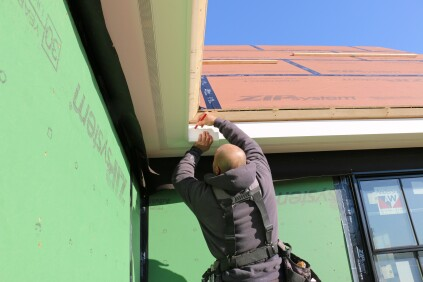 Using a gauging block to draw a line for the bottom of the crown molding ensures its accurate placement.