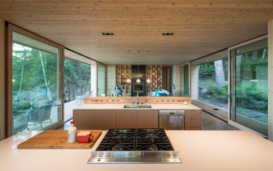 The open-plan kitchen and living and dining rooms are lined in wood paneling and custom, built-in shelves that connect the interior to the forest outside.