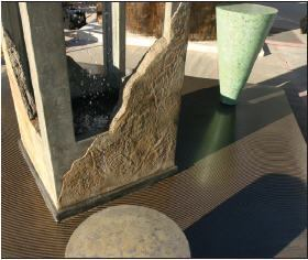 Becker precast a monument-styled water feature, resting it on a slab with colored bands of microtopping patterned with stenciling techniques.