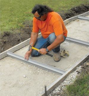When placed in the sidewalk at regular jointing intervals, the diamond-shaped TripStop forms a double-keyed joint, allowing the sidewalk to articulate around the product. The joints can be cut onsite using a fine handsaw or with a combination saw with a fine-tooth blade. The product is secured with steel pegs driven through pre-drilled holes prior to the concrete pour. Photo: Jonathan Gano