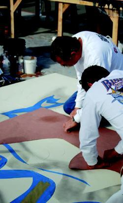 At the 2006 Artistry Demo one of the presenters is cutting a stencil onsite for use with a thin overlay cement graphic.