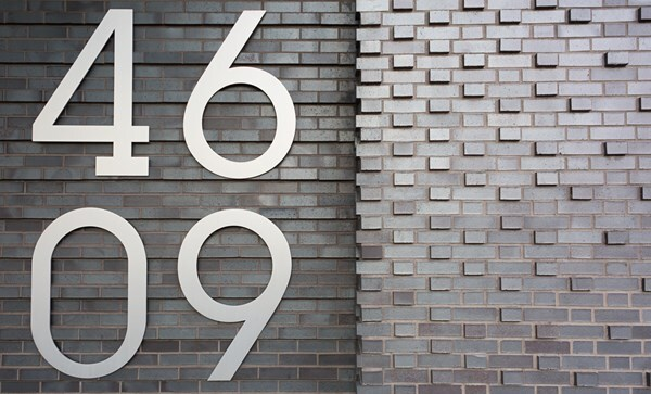 An address plaque on the façade of 46-09 Eleventh St, in Long Island City, N.Y.