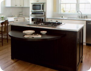 The height of the curved tabletop is designed to work with standard dining room chairs instead of bar stools. In addition to the folding top, the furniture-look island also holds a downdraft cooktop with drawers on either side. The charcoal stain provides a dramatic contrast with the surrounding white cabinets and white-marble countertops.