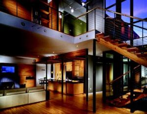 INDUSTRIAL STRENGTH: Inside, warm woods are offset by 6-inch, steel pipe columns, open cable railings, and  a muscular fireplace surround of 1-inch ceramic tile. The round  vents of a high-pressure HVAC system (seen in the ceiling fascia) serve as  aesthetic elements in their own right.