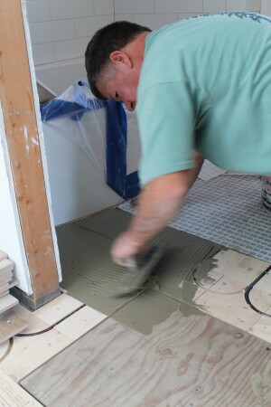 Radiant flooring panels are an excellent choice under a tiled floor. Here, the tile installer applies mortar for the separation membrane that is installed before the tile.