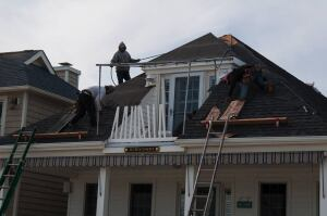 A Brielle New Jersey home receives a new roof post Hurricane Sandy. While flood damage predominated in shore communities, some wind damage did occur. But careful case-by-case inspection may be required to determine how much damage can be attributed to which factor.