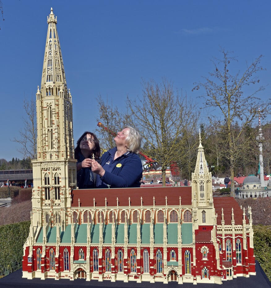 Model designers Vera Feldmann and Anastasia Trautwein stand by a replica of Ulm cathedral at Legoland Germany. The scale model of the world's largest church tower took 4 months and over 112,000 Lego bricks to build.