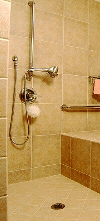 The customized curbless shower includes a transfer bench and strategically located grab bars.