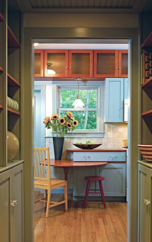 Cabinets placed above the windows in this high-ceilinged kitchen add storage and create deep nooks similar in feel to protruding window bays.