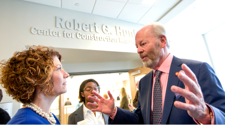 Robert G. Hunt (right) speaks with Jennifer Bott, dean of the Miller College of Business, outside of the new center at Ball State.