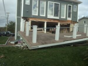 Ripped from the wall, a damaged second-floor deck sits on the ground in front of a house in Norfolk, Conn.